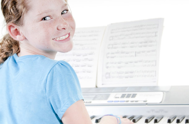 Young girl smiling taking piano lessons.
